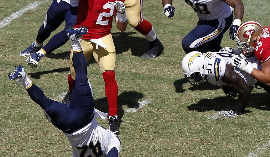San Francisco 49ers quarterback Blaine Gabbert (2) passes as running back LaMichael James (23) blocks San Diego Chargers cornerback Chris Davis (42) during the third quarter of an NFL preseason football game in Santa Clara, Calif., Sunday, Aug. 24, 2014. (AP Photo/Mathew Sumner)