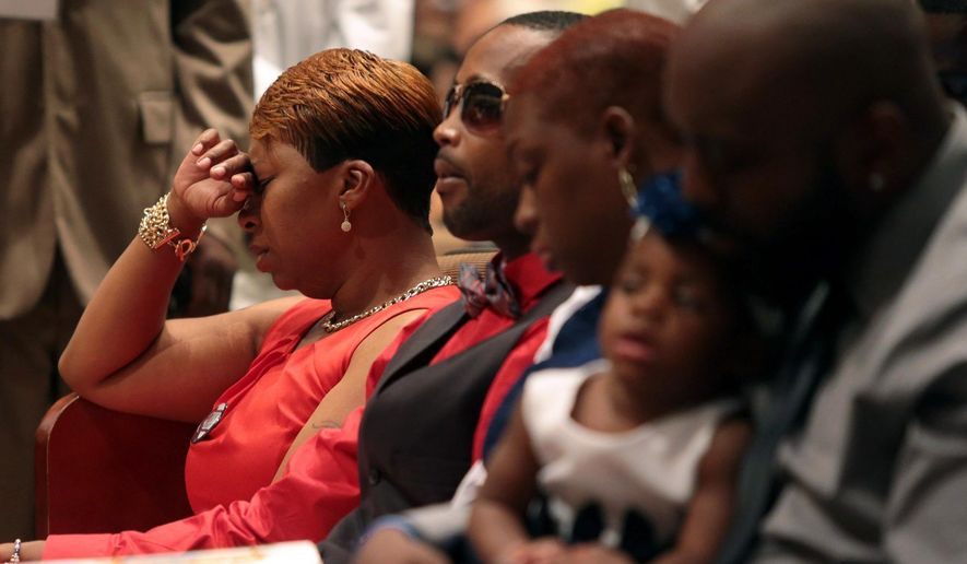Lesley McSpadden, left, Michael Brown's mother, closes her eyes during the funeral service for her son, Monday, Aug. 25, 2014, at Friendly Temple Missionary Baptist Church in St. Louis. Hundreds of people gathered to say goodbye to Brown, who was shot and killed by a Ferguson, Mo., police officer on Aug. 9. (AP Photo/St. Louis Post Dispatch, Robert Cohen, Pool)