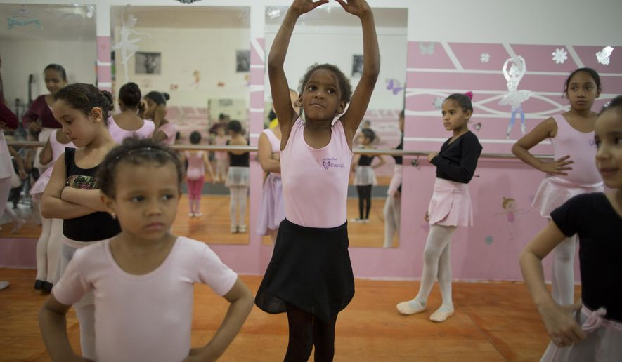 In this Aug. 8, 2014 photo, girls participate in a ballet class at the House of Dreams dance studio in Crackland, one of the roughest neighborhoods in downtown Sao Paulo, Brazil. Growing up amid drug dealers and addicts, some girls have yet to learn how to read. Yet they are learning the graceful art of ballet courtesy of a local church group that also offers them food, counseling and Bible studies. (AP Photo/Andre Penner)