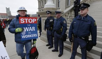 FILE - In this Dec. 11, 2012 file photo, a protester, wearing a Michigan Education Association helmet, walks past Michigan State Police at the State Capitol in Lansing, Mich., in an unsuccessful effort to block passage of right-to-work legislation that bans labor agreements that require employees to pay fees to the unions that represent them. Organized labor and pro-business groups are waging an intense lobbying campaign directed at Michigan teachers who will decide whether to remain in their union. The teachers' decisions will be the first big test of the state's new right-to-work law. (AP Photo/Paul Sancya)