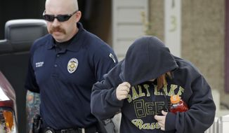 A unidentified woman is escorted from a home by a police officer after a baby was found in a garbage can in Kearns, Utah on Tuesday, Aug. 26, 2014. Police say the newborn is in extremely critical condition he was left in a trash can near his mother's home. Unified Police Detective Jared Richardson says a woman who lived nearby heard what she thought was a kitten meowing in the trash bin on Tuesday morning. (AP Photo/Rick Bowmer)