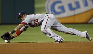 Washington Nationals shortstop Ian Desmond dives for a ground out by Philadelphia Phillies' Carlos Ruiz during the fourth inning of a baseball game, Tuesday, Aug. 26, 2014, in Philadelphia. (AP Photo/Matt Slocum)