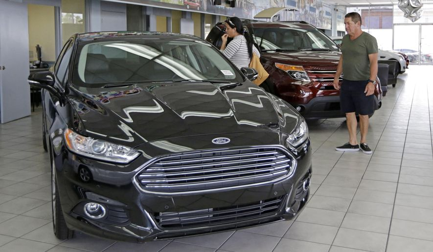 In this photo taken Aug. 21, 2014, Orestes Perez, right, and his niece Yanuska Perez, check a 2013 Ford Fusion SE at a local dealership in Hialeah, Fla. The Commerce Department reports on business orders for durable goods in July on Tuesday, Aug. 26, 2014. (AP Photo/Alan Diaz)