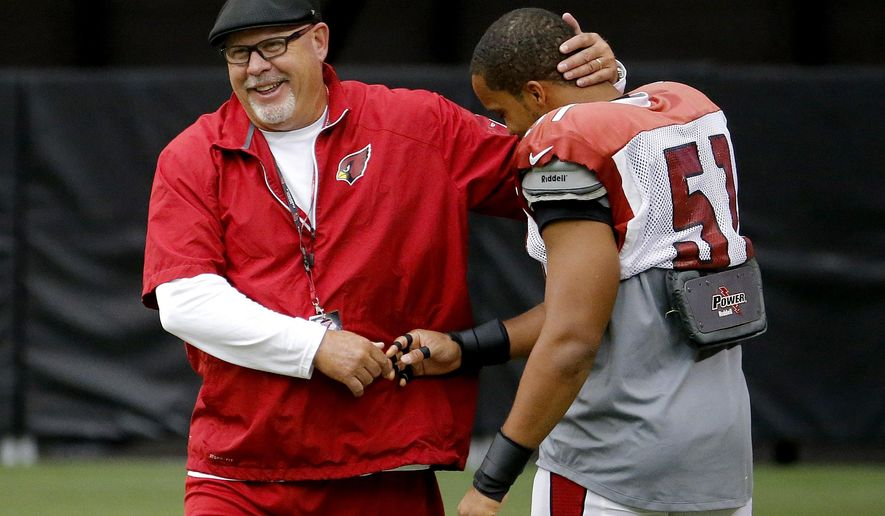 FILE - In this July 28, 2014, file photo, Arizona Cardinals head coach Bruce Arians, left, greets Kevin Minter (51) during an NFL football training camp in Glendale, Ariz.  The Arizona Cardinals have hired Jen Welter to coach inside linebackers through their upcoming training camp and preseason. The Cardinals say Welter is believed to be the first woman to hold a coaching position of any kind in the NFL.  (AP Photo/Matt York, File) **FILE**