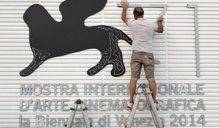 Enricco Masserdotti prepares a sign for the 71st edition of the Venice Film Festival in Venice, Italy, Monday, Aug. 25, 2014. The 71st edition of the festival opens on Wednesday, Aug. 27 and runs until Sept. 6. (AP Photo/David Azia)