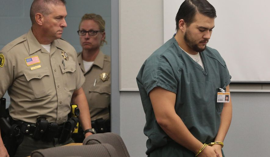 Christopher Lee, right, is escorted into the courtroom for a hearing Tuesday, Aug. 26, 2014,  in Joshua Tree, Calif. Lee is charged with murder in the death of Erin Corwin, a fellow Marine's pregnant wife. (AP Photo/The Desert Sun, Richard Lui)  RIVERSIDE PRESS-ENTERPRISE OUT;  NO SALES; NO FOREIGN
