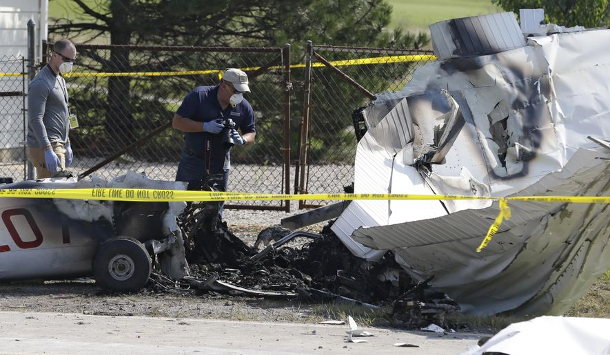 Investigators look over the wreckage of a plane that crashed as it rests on the side of a road Tuesday, Aug. 26, 2014, in Richmond Heights, Ohio. The Cessna 172R crashed and burst into flames just after takeoff from a regional airport outside of Cleveland on Monday, killing all four people on board, according to the Ohio State Highway Patrol. (AP Photo/Tony Dejak)