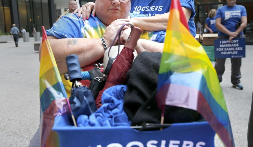 Bonnie Everly, left, and Lyn Judkins, from Chesterton, Ind., embrace during a rally in support of gay marriage at the federal plaza Monday, Aug. 25, 2014, in Chicago. The Chicago-based 7th U.S. Circuit Court of Appeals will hear arguments Tuesday, Aug. 26, on gay marriage fights from Indiana and Wisconsin, setting the stage for one ruling. Each case deals with whether statewide gay marriage bans violate the Constitution. (AP Photo/Charles Rex Arbogast)