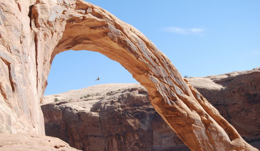 FILE - This Nov. 4, 2012, file photo, shows an unidentified person swinging from the Corona Arch near Moab, Utah. The federal government is asking for people to weigh in on whether it should temporarily ban daredevil rope swinging and other activities from iconic arches in Moab. The Bureau of Land Management says rope recreation at Corona Arch and Gemini Bridges may be disturbing other people in popular hiking areas that each get more than 40,000 visitors a year. The BLM is accepting written and emailed comments through Sept. 25, 2014. (AP Photo/The Salt Lake Tribune, Brian Maffly) DESERET NEWS OUT; LOCAL TV OUT; MAGS OUT