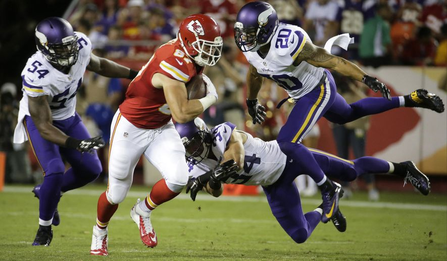 Kansas City Chiefs tight end Travis Kelce (87) runs from Minnesota Vikings safety Kurt Coleman (20), linebacker Jasper Brinkley (54) and safety Andrew Sendejo (34) during the second half of an NFL preseason football game in Kansas City, Mo., Saturday, Aug. 23, 2014. The Vikings won 30-12. (AP Photo/Charlie Riedel)