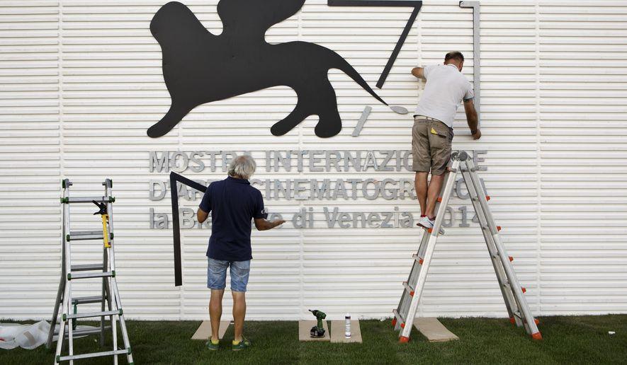 Enricco Masserdotti, right, and his colleague Carlo Gheda prepare a sign for the 71st edition of the Venice Film Festival in Venice, Italy, Monday, Aug. 25, 2014. The 71st edition of the festival opens on Wednesday, Aug. 27 and runs until Sept. 6. (AP Photo/David Azia)