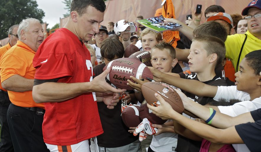 In this Aug. 12, 2014 photo, Cleveland Browns quarterback Johnny Manziel signs for  fans after practice at NFL football training camp in Berea, Ohio. Manziel doesn't view himself as the Browns' savior, but almost everyone else does. The dynamic rookie quarterback will begin the season as Cleveland's second-string quarterback, but it may not be long before he's moved ahead of Brian Hoyer, who already seems to be looking over his shoulder. (AP Photo/Mark Duncan)