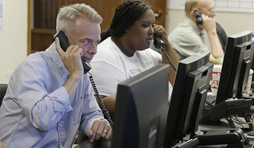 Former state Sen. Steve Russell, left, candidate for the Republican nomination to a congressional seat in central Oklahoma, works the phones along with campaign volunteers Crystal Griffin, center, and Larry Carr, right, in Oklahoma City, Monday, Aug. 25, 2014, as candidates facing runoffs in Oklahoma's primary worked through last-day chores to ensure that those who voted for them two months ago will make it back to the polls. (AP Photo/Sue Ogrocki)