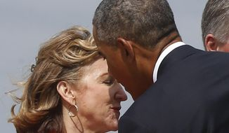 President Barack Obama is greeted by Sen. Kay Hagan, D-N.C., left, who has criticized the Obama administration on veterans issues, as he arrives at North Carolina Air National Guard Base in Charlotte, N.C., Tuesday, Aug. 26, 2014. Obama is in Charlotte to address the American Legion's 96th National Convention. (AP Photo/Charles Dharapak)