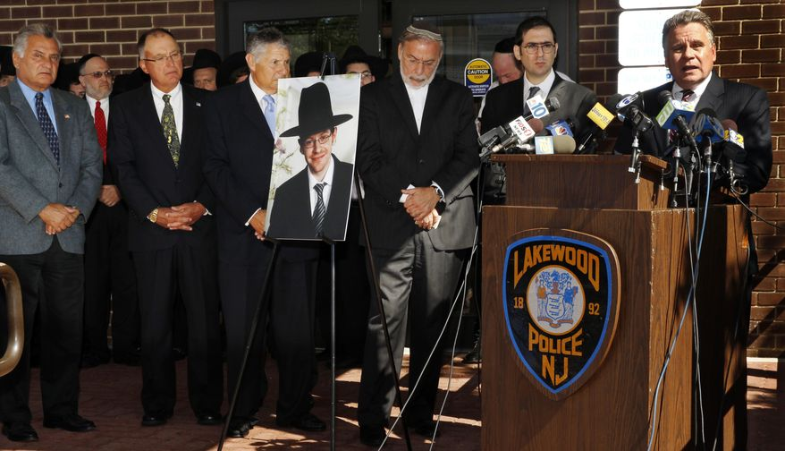 U.S. Rep. Chris Smith, right, R-NJ, addresses a gathering as he stands near a photograph of Aaron Sofer, center, 23, Tuesday, Aug. 26, 2014, in Lakewood, N.J. Israeli police said Tuesday they are searching for the young New Jersey religious student who went missing in Israel during a hike in a forest outside Jerusalem last week. Sofer of Lakewood, New Jersey, has been missing since Friday when he went on a hike with a friend in the Jerusalem Forest, said police spokesman Micky Rosenfeld. (AP Photo/Mel Evans)
