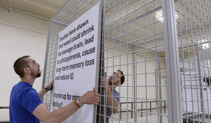 "In an Aug. 8, 2014 photo, crew members Andrew Willey, left, and Brian Houchin at Proctor Productions, Inc. in Denver finish assembling large cages, for the ""Don't be a Lab Rat"" advertising campaign by the state through Sukle Advertising designed to keep kids from using marijuana.  The provocative anti-marijuana campaign aimed at Colorado youths has angered marijuana activists for its tag line, ""Don't Be a Lab Rat."" Now, the Boulder Valley School District is declining to display a human-size cage used in the campaign. Instead, the cage will be displayed near a city park through Sept. 15. (AP Photo/The Denver Post, Kathryn Scott Osler)"