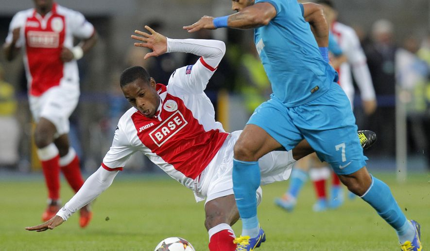 Standard de Liege's Ricardo Faty, left, fights for the ball with Zenit's Hulk during the UEFA Champions League, play offs, 2nd leg soccer match, between Standard de Liege  and Zenit St. Petersburg in St.Petersburg, Russia, Tuesday, Aug. 26, 2014. (AP Photo/Dmitry Lovetsky)