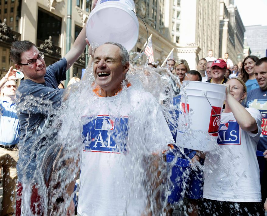 participates in the ALS Ice-Bucket Challenge outside the organization's headquarters in New York, Wednesday, Aug. 20, 2014. Manfred participated with more than 160 other MLB employees to raise more than $16,000 for the ALS Association. (AP Photo/Vanessa A. Alvarez)