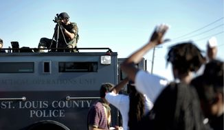 A member of the St. Louis County Police Department aims at a group of protesters in Ferguson, Missouri. Pundits are suggesting the Michael Brown incident, although not unique, opened a discussion not only on race relations but also on police militarization. (Associated Press)