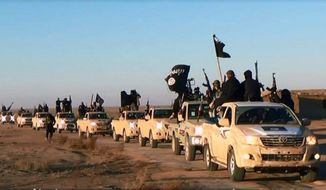 A convoy of vehicles and militant fighters  move through Iraq's Anbar Province. The U.S. government is tracking and gathering intelligence on as many as 300 Americans who are fighting side-by-side with the Islamic State group in Iraq and Syria and are poised to become a major threat to the homeland, according to senior U.S. officials. (Associated Press)