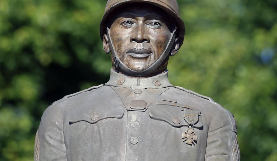 FILE - In this July 10, 2014 file photo, a statue of Henry Johnson is displayed in the Arbor Hill neighborhood in Albany, N.Y. The secretary of defense has recommended awarding a posthumous Medal of Honor to the black soldier from upstate New York who saved a comrade while fighting off a German attack in France during World War I. Sen. Charles Schumer says Tuesday that Chuck Hagel has sent Congress a letter saying Sgt. Henry Johnson should receive the nation's highest military decoration for bravery in combat. (AP Photo/Mike Groll, File)
