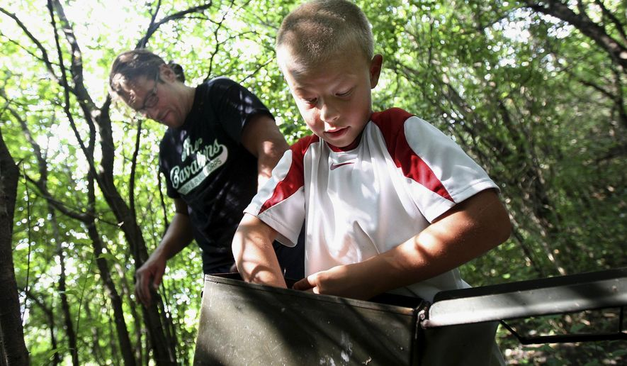 In this Aug. 1, 2014 photo, Jonny Locascio, 8, of Sycamore, Ill., opens a cache he and his dad, Greg Locascio, found while geocaching in DeKalb, Ill. Greg Locascio has been teaching his son about the game after playing himself since 2012. Starting to geocache can be as simple as downloading a free application to a smartphone or jotting down coordinates from a geocaching website. (AP Photo/Daily Chronicle, Monica Maschak)  MANDATORY CREDIT