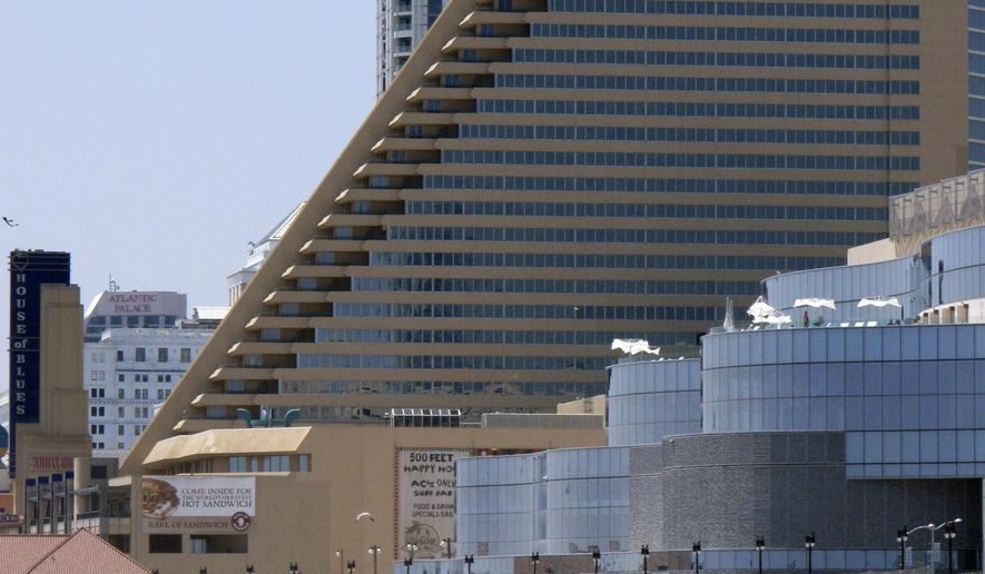 In this photo taken on July 23, 2014, people play on the beach in Atlantic City N.J., near of the Showboat Casino Hotel, center, Revel, foreground right, and Trump Plaza, background top. Showboat and Revel are expected to shutdown this weekend. Trump Plaza will close on Sept. 16. Nearly 8,000 workers will lose their jobs when the three casinos shut down. Atlantic City is planning additional job training as three casinos prepare to shut down over the next few weeks, putting thousands of workers on the street. (AP Photo/Wayne Parry)