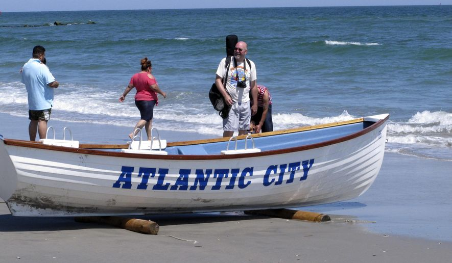 This June 16, 2014, photo shows people walking along the water's edge in Atlantic City, N.J. As three casinos prepare to shut down over the labor Day weekend, city and tourism officials are stressing the many non-gambling attractions that Atlantic City still offers. (AP Photo/Wayne Parry)