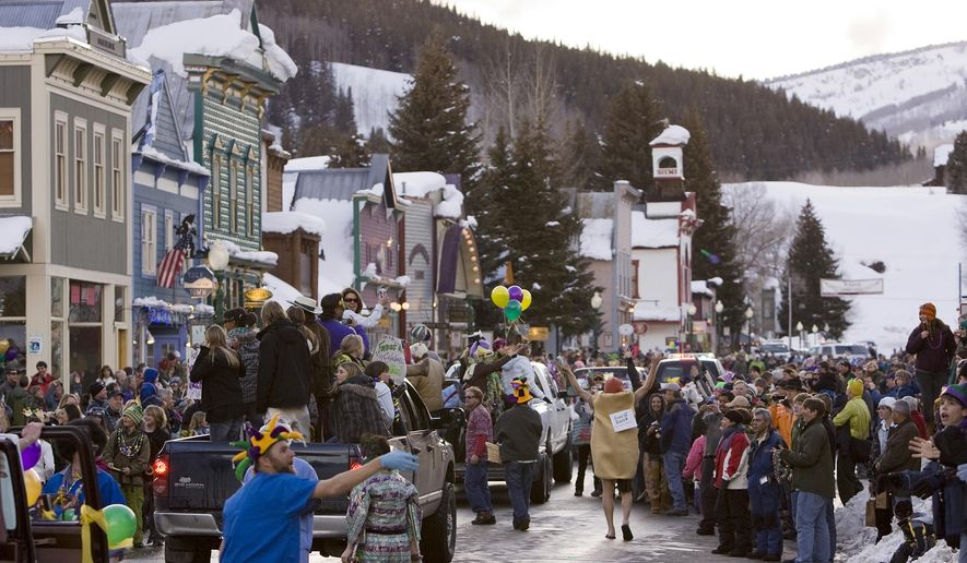 FILE - In this Feb. 24, 2009 file photo, a crowd gathers on Elk Avenue in Crested Butte, Colo., during a Mardi Gras parade celebration. Some people in normally laid back Crested Butte, are not up for a secretive Bud Light plan to paint their mountain town blue and turn it into a fantasy town for an ad campaign. The Denver Post reports the company has agreed to pay the town $250,000 to fence off its main street and bring in more than 1,000 revelers for the Sept. 5-7 event. (AP Photo/Nathan Bilow, File)