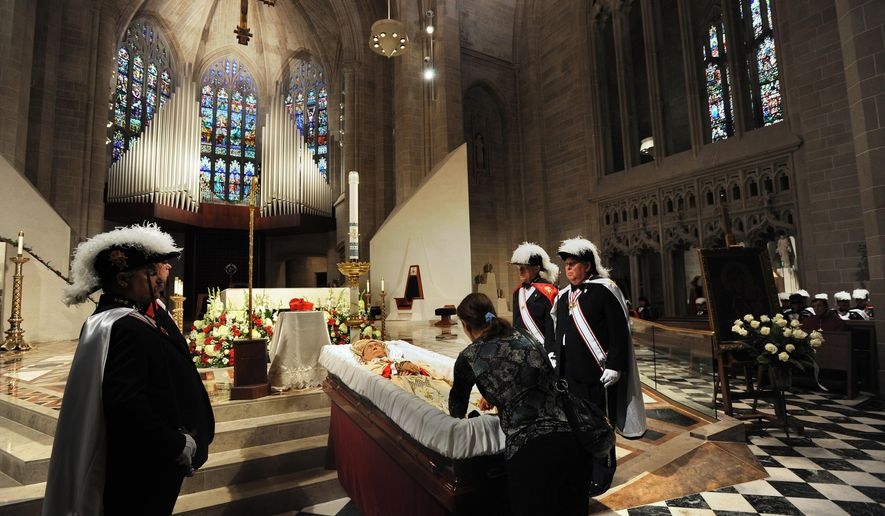 "Knights of Columbus stand guard as Ann Kassab, center, touches a rosary to Cardinal Edmund Szoka's clothes, asArchbishop Allen H. Vigneron presides over the ""Reception of the Body"" of Cardinal Edmund Szoka, who died this week at 86, at the Cathedral of the Most Blessed Sacrament in Detroit, on Sunday, Aug. 24, 2014. The ceremony proceeded Szoka's visitation. (AP Photo/The Detroit News, Brandy Baker)"