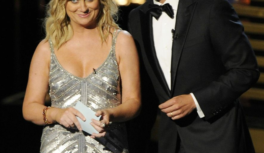 Amy Poehler, left, and Host Seth Meyers speak on stage at the 66th Annual Primetime Emmy Awards at the Nokia Theatre L.A. Live on Monday, Aug. 25, 2014, in Los Angeles. (Photo by Chris Pizzello/Invision/AP)