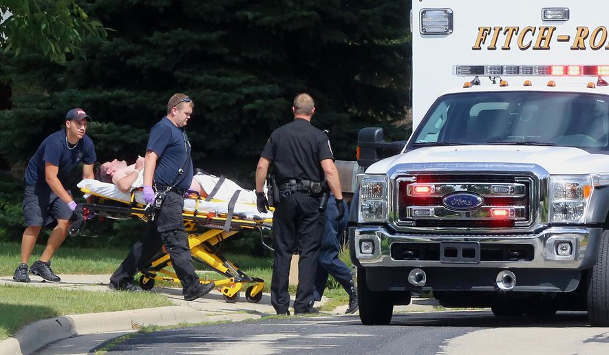 FILE - In this Aug. 22, 2014 file photo emergency personnel transport Andy Steele from his home in Fitchburg, Wis., where authorities said Steele's wife, Ashlee Steele and sister-in-law, Kacee Tollesfsbol, were found shot dead. Authorities said Tuesday, Aug. 26, 2014 that Tollefsbol called 911 around 1 p.m. Friday and said Andy Steele had shot her in the back. Andy Steele was arrested but hasn't been charged. (AP Photo/Wisconsin State Journal, John Hart, File)
