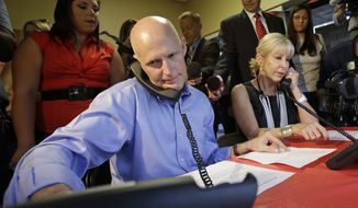 Florida Gov. Rick Scott, left, and his wife Ann make calls to supporters during a visit to a phone bank field office, Tuesday, Aug. 26, 2014, in Orlando, Fla. Scott is seeking re-election for a second term as Florida's governor. (AP Photo/John Raoux)