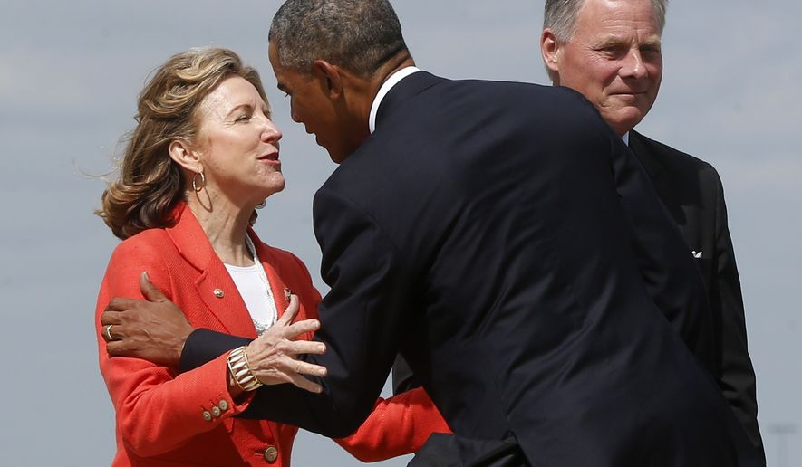 President Barack Obama is greeted by Sen. Kay Hagan, D-N.C., left, who has criticized the Obama administration on veterans issues, as he arrives at North Carolina Air National Guard Base in Charlotte, N.C., Tuesday, Aug. 26, 2014. Obama is in Charlotte to address the American Legion's 96th National Convention. At right is Sen. Richard Burr, R-N.C. (AP Photo/Charles Dharapak)