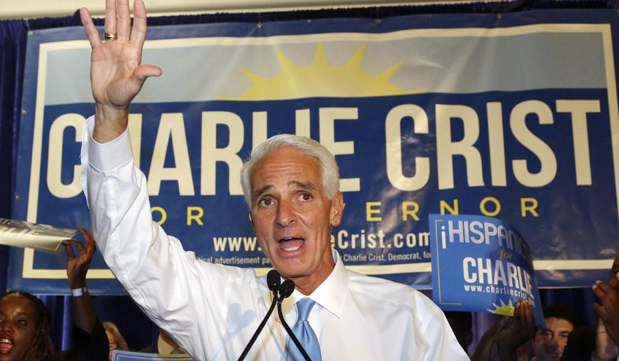 Former Republican Gov. Charlie Crist waves to supporters while speaking at a victory party after Florida's primary election, Tuesday, Aug. 26, 2014 in Fort Lauderdale, Fla. Crist defeated Nan Rich, a former Senate Democratic leader who has been campaigning for governor longer than Crist has been a Democrat. He is the first person in Florida to win the nomination for governor as a Republican and a Democrat. At right is Crist's wife Carole. (AP Photo/Wilfredo Lee)