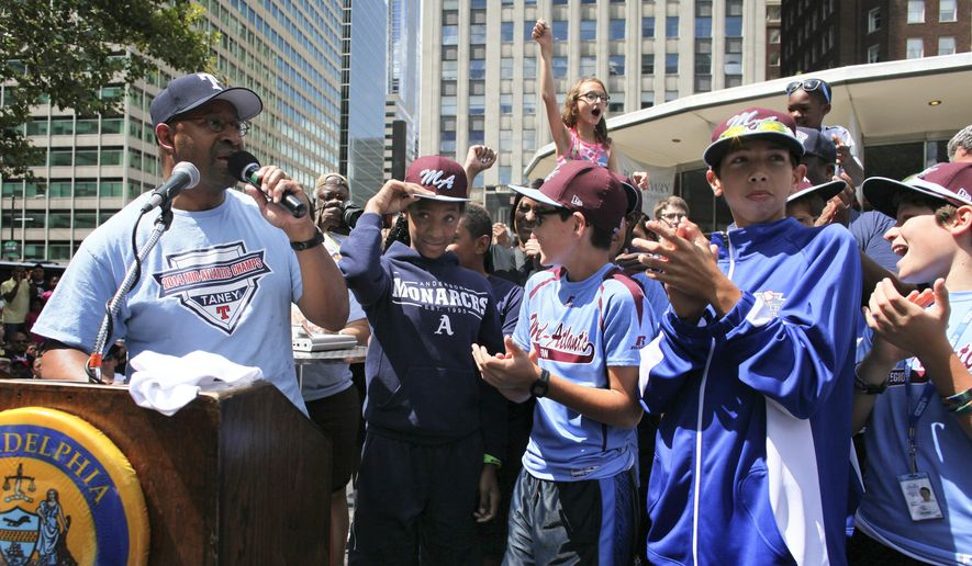 FILE - In this Sunday, Aug. 24, 2014, file photo, Philadelphia Mayor Michael Nutter, left, introduces members of the Taney Dragons as they are greeted by fans and city officials during a rally to celebrate the team's return to Philadelphia after competing in the Little League World Series. (AP Photo/Joseph Kaczmarek)