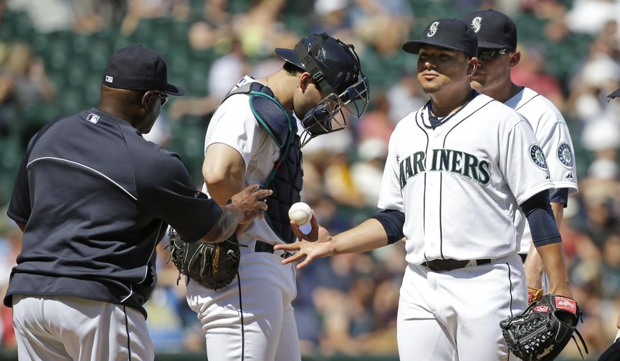Seattle Mariners starting pitcher Erasmo Ramirez hands the ball over to manager Lloyd McClendon, left, while being relieved against the Texas Rangers in the fourth inning of a baseball game Wednesday, Aug. 27, 2014, in Seattle. AP Photo/Elaine Thompson)