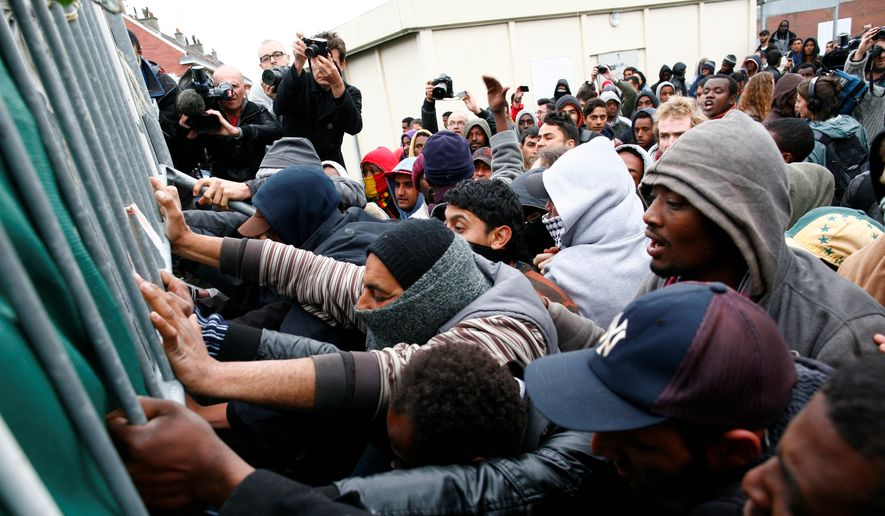 Seeking asylum: Migrants and activists scuffle with police after authorities started to clear out makeshift camps in Calais, France on the English Channel on May 28, 2014. Officials blame a British-French pact for burdening the city with immigrants seeking British asylum. (Associated Press) **FILE**