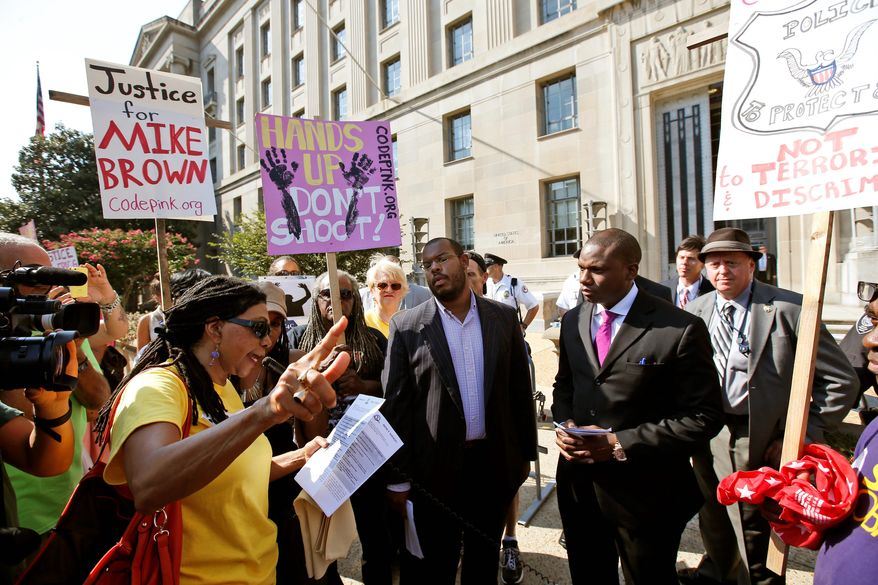 Justice Department spokesman Kevin Lewis (second from right) listens as Marsha Coleman-Adebayo reads a letter during a rally. (Associated Press photographs)
