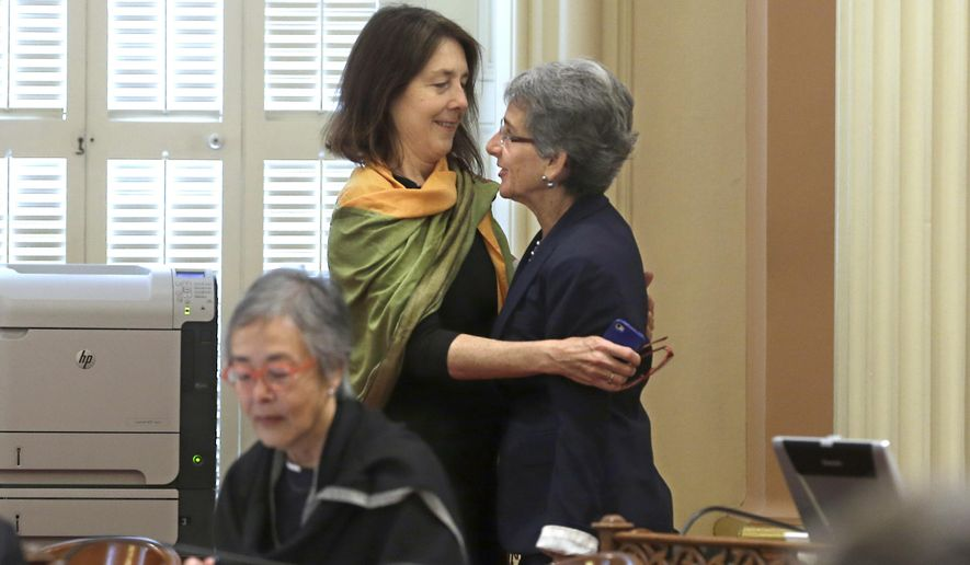 """Assemblywoman Nancy Skinner, D-Berkeley, left, hugs State Sen. Hannah-Beth Jackson, D-Santa Barbara, after the bill they co-authored, along with Assemblyman Das Williams, D-Santa Barbara, that will allow courts to issue temporary """"gun violence restraint order"""" was approved by the Senate at the Capitol in Sacramento, Calif., Wednesday, Aug. 27, 2014. The bill, AB1014, was drafted in response to the mass shootings near the University of California, Santa Barbara last May, will allow law enforcement and immediate family members to seek a restraining order removing fire arms for 21 days. (AP Photo/Rich Pedroncelli)"""