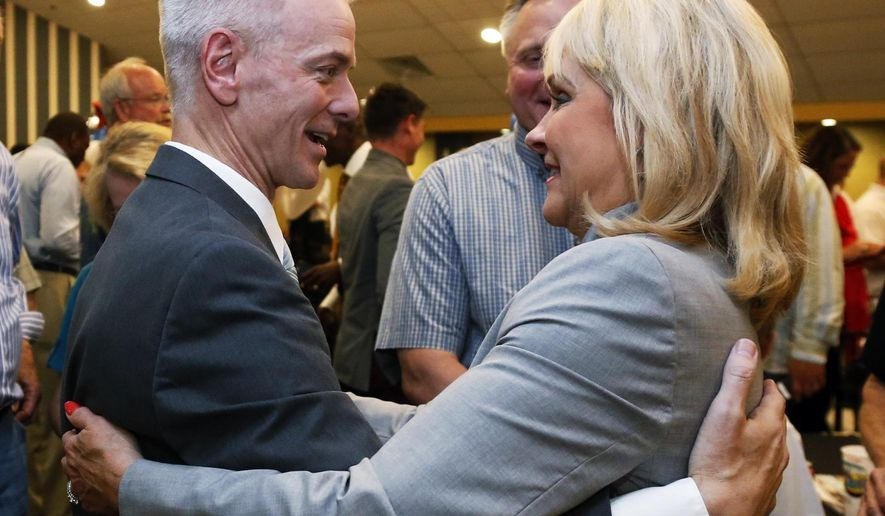 Former state Sen. Steve Russell, left, candidate for the Republican nomination to a congressional seat in central Oklahoma, embraces Oklahoma Gov. Mary Fallin, right, at his watch party in Oklahoma City, Tuesday, Aug. 26, 2014. (AP Photo/Sue Ogrocki)
