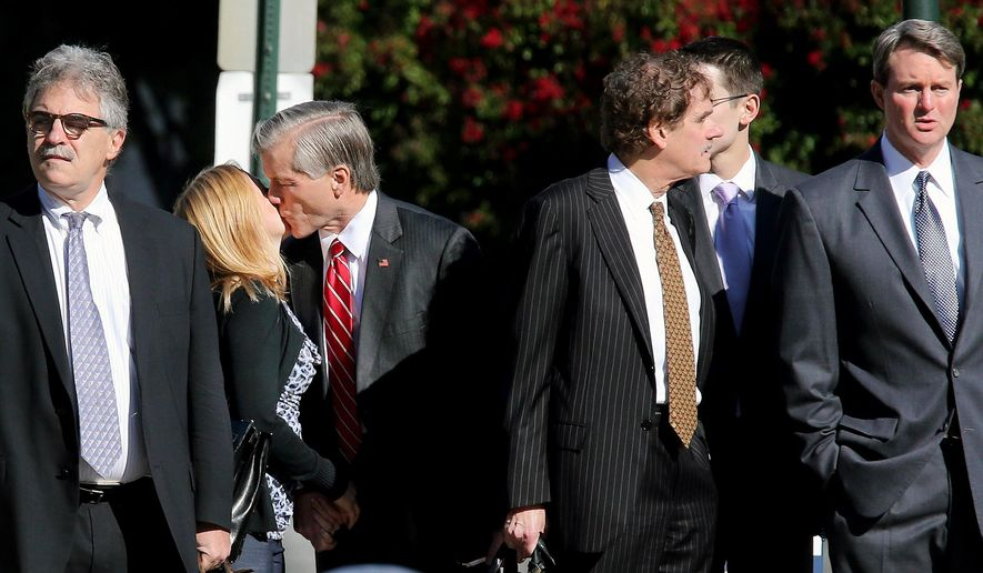 Former Virginia Gov. Bob McDonnell, third from left, gives his daughter, Cailin Young, second from left, a kiss as they and, from left, attorney Daniel Small, attorney Henry W. Asbill, son in law Chris Young (partially hidden) and attorney John L. Brownlee wait to cross the street on the way to the federal courthouse in Richmond, Va., Tuesday, Aug. 26, 2014 where the federal corruption trial against the former governor and former first lady Maureen McDonnell continues into its fifth week. (AP Photo/Richmond Times-Dispatch, Bob Brown)