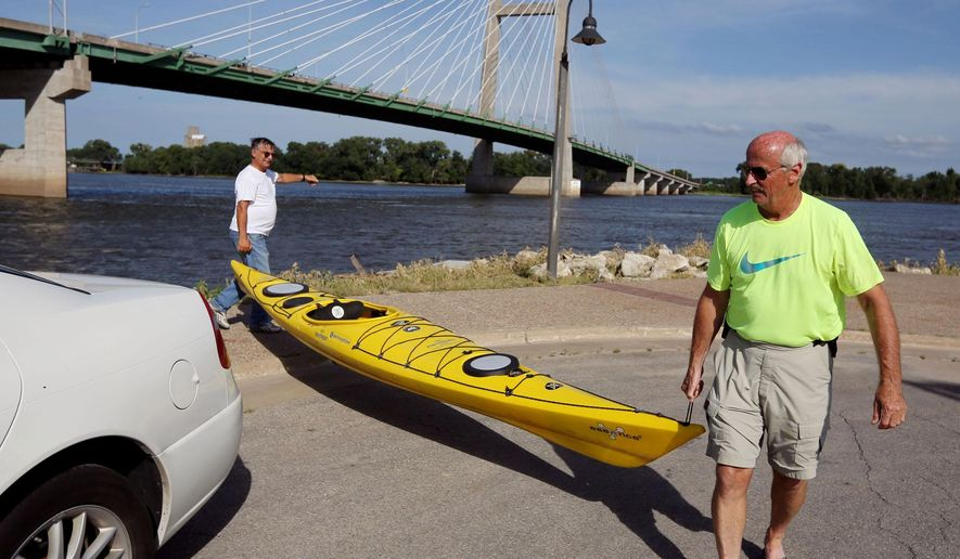 In this photo taking on Tuesday, Aug. 26, 2014, John Hatch, front, who is kayaking down the Mississippi to raise awareness and money for breast cancer research, loads his kayak onto the top a car with the help of friend Larry Humphrey along the Mississippi River front in Burlington, Iowa. Hatch was forced to take a break from his trip down the river after his kayak was vandalized Monday evening. (AP Photo/The Hawk Eye, John Lovretta)