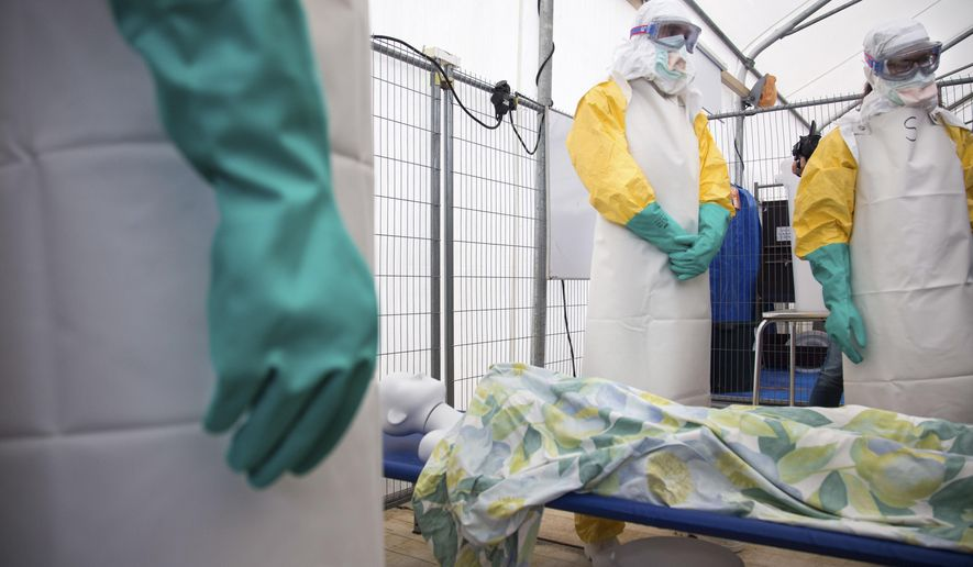 During a training session participants listen as they stand over a mannequin on a stretcher during a training course to instruct non-governmental organisation (NGO) workers and doctors on how to deal with the Ebola virus in Brussels on Tuesday, Aug. 26, 2014. The course, provided by Doctors Without Borders, trains volunteer and medical personnel on precautions to take when entering a zone that contains the Ebola virus.(AP Photo/Olivier Matthys)