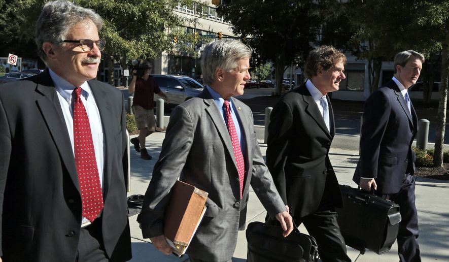 Former Virginia Gov. Bob McDonnell, second from left, arrives at federal court with his attorneys Danial Small, left, Henry Asbill second from right, and John Brownlee, right,  Wednesday, Aug. 27, 2014, in Richmond, Va.,  The defense in his corruption case is expected to rest today. McDonnell and his wife, Maureen, are charged with accepting more than $165,000 in gifts and loans from former Star Scientific Inc. CEO Jonnie Williams in exchange for promoting his company's dietary supplements.  (AP Photo/Steve Helber)