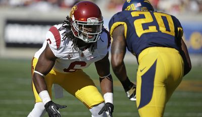 FILE - In this Nov. 9, 2013, file photo, Southern California cornerback Josh Shaw, left, lines up against California defensive back Isaac Lapite during the first quarter of an NCAA college football game in Berkeley, Calif. Shaw injured both ankles after leaping from a second-story balcony to save his 7-year-old nephew, Carter, from drowning in a pool. Shaw was named a team captain on Saturday, Aug. 23, 2014, and later that night was attending a family function at a cousin's apartment in his hometown of Palmdale when he saw his nephew, who can't swim, struggling in the pool. (AP Photo/Eric Risberg, File)