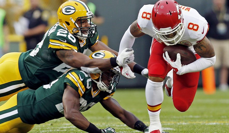 Green Bay Packers' Sean Richardson (28) and Jumal Rolle (20) try to stop Kansas City Chiefs' Albert Wilson (8) during the first half of an NFL football preseason game Thursday, Aug. 28, 2014, in Green Bay, Wis. (AP Photo/Mike Roemer)
