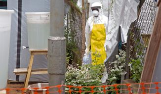 This Aug. 12, 2014, file photo shows a health care worker walking near a Ebola isolation unit wearing protective gear against the virus at Kenema Government Hospital in Kenema, Sierra Leone. (AP Photo/ Michael Duff, File) ** FILE **