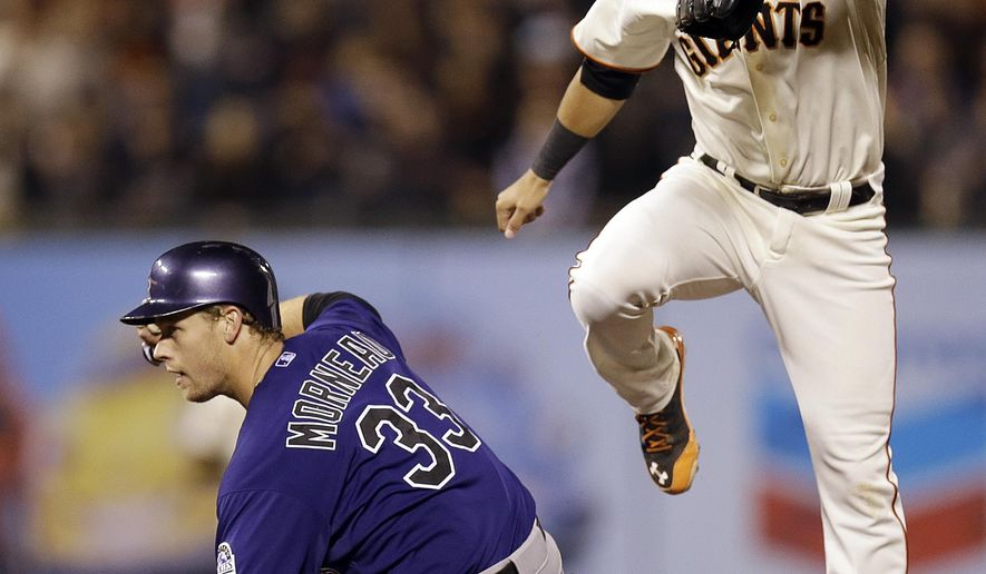 San Francisco Giants' Joe Panik, right, hops over Colorado Rockies' Justin Morneau (33) after completing a double play in the fourth inning of a baseball game Wednesday, Aug. 27, 2014, in San Francisco. Nolan Arenado was out at first base. (AP Photo/Ben Margot)