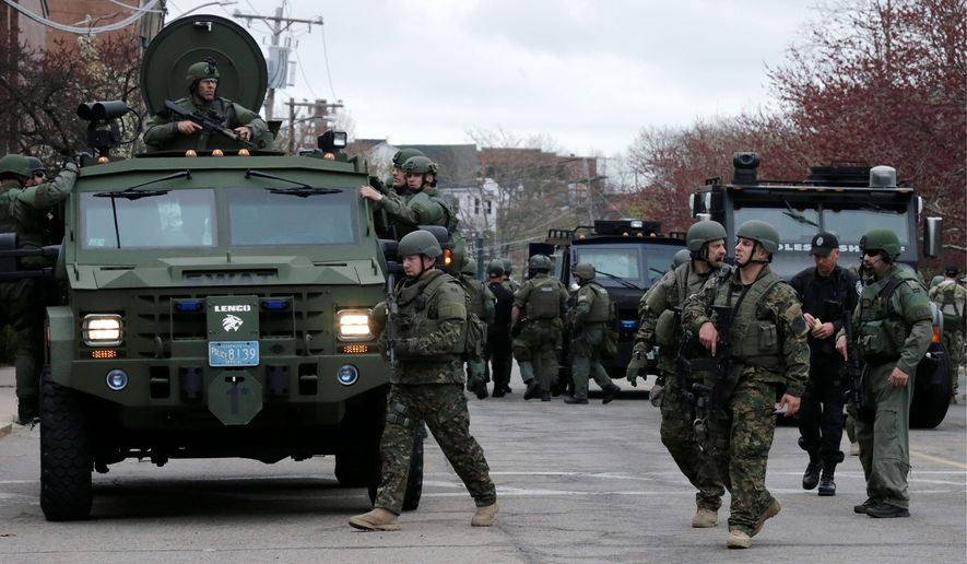 A SWAT team unloads from armored vehicles as they go door to door while searching for a suspect in the Boston Marathon bombings in Watertown, Massachusetts.